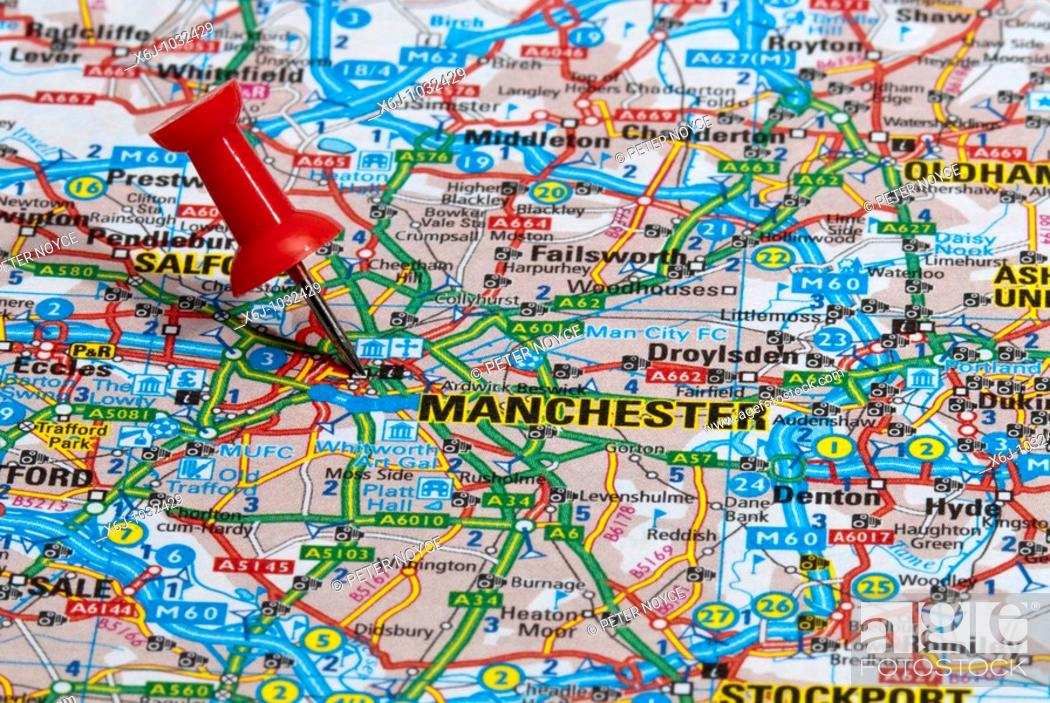 Stock Photo: red map pin in road map pointing to city of Manchester.