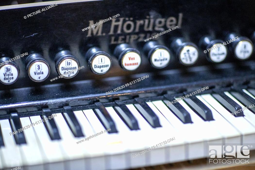 """Stock Photo: 22 June 2020, Mecklenburg-Western Pomerania, Rostock: The keyboard of a harmonium from the 1930s is restored in the workshop """"""""Historical Keyboard Instruments -."""