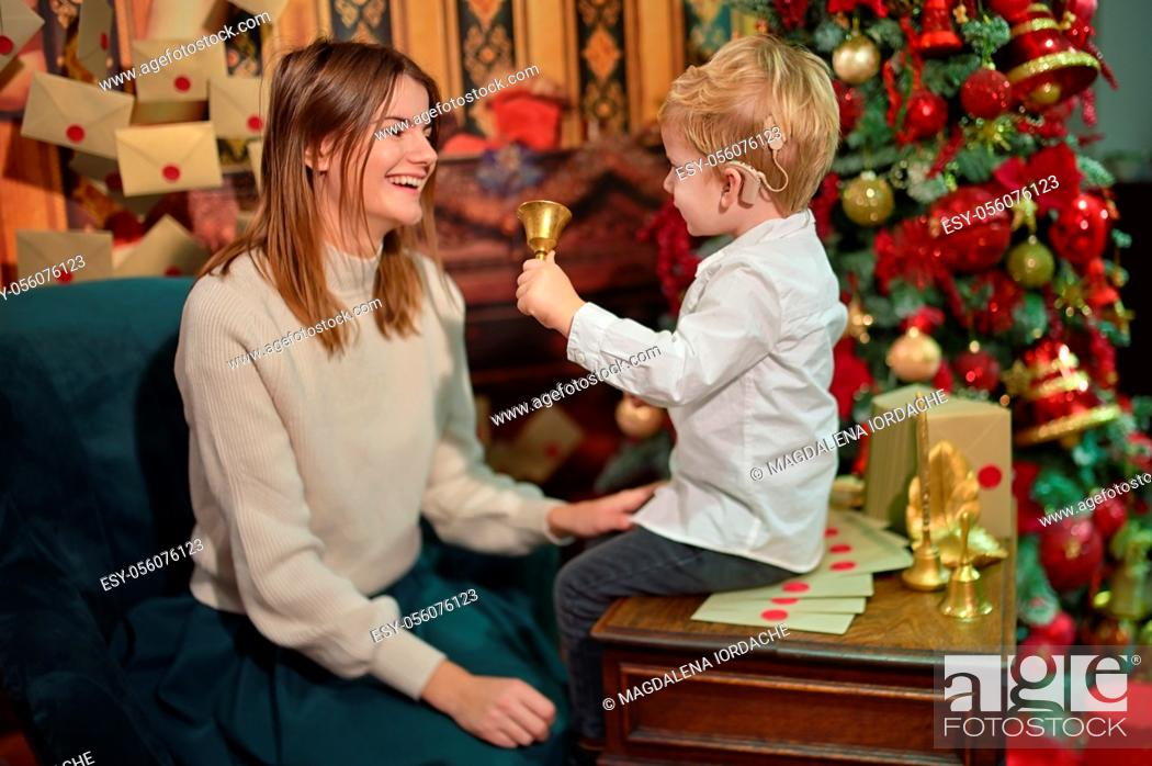 Stock Photo: A Boy with Cochlear Implants play with Christmas Bell with his Mother.