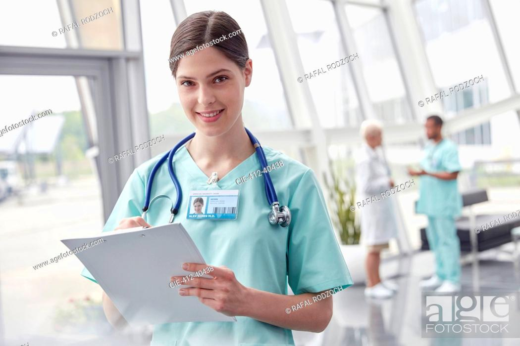 Photo de stock: Portrait smiling, confident female nurse with clipboard in hospital.