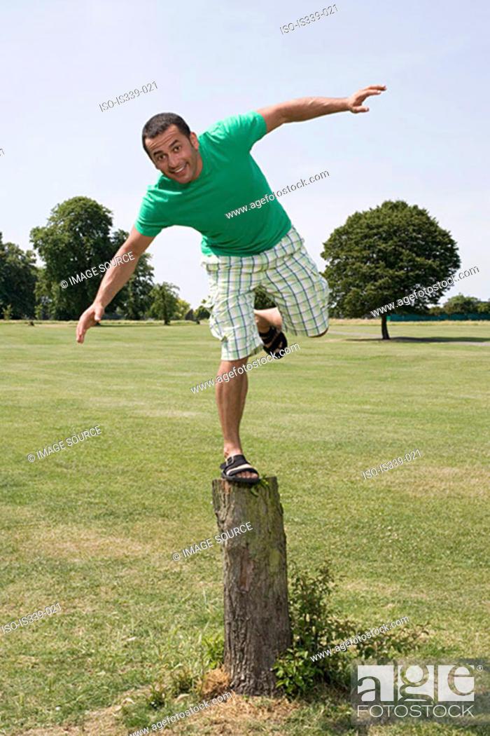 Stock Photo: Man balancing on tree stump.