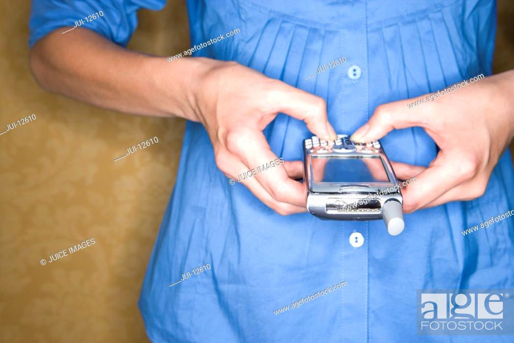 Stock Photo: Woman using mobile phone, mid section, close-up.