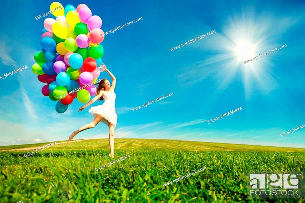 Stock Photo: Happy birthday woman against the sky with rainbow-colored air balloons in her hands. sunny and positive energy of nature.