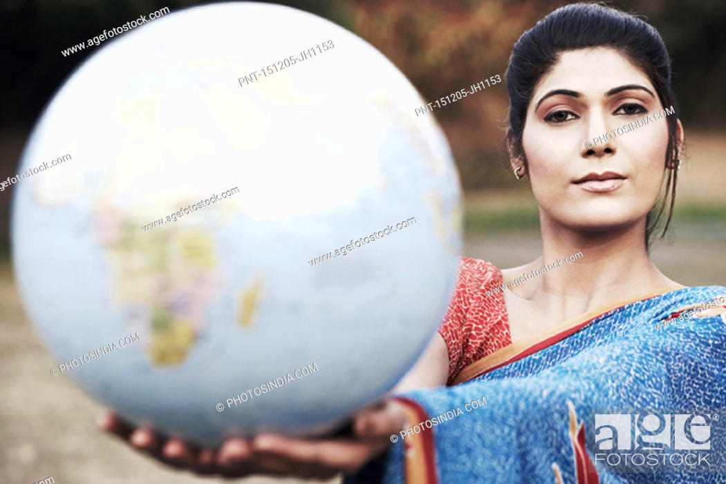 Stock Photo: Portrait of a young woman holding a globe.