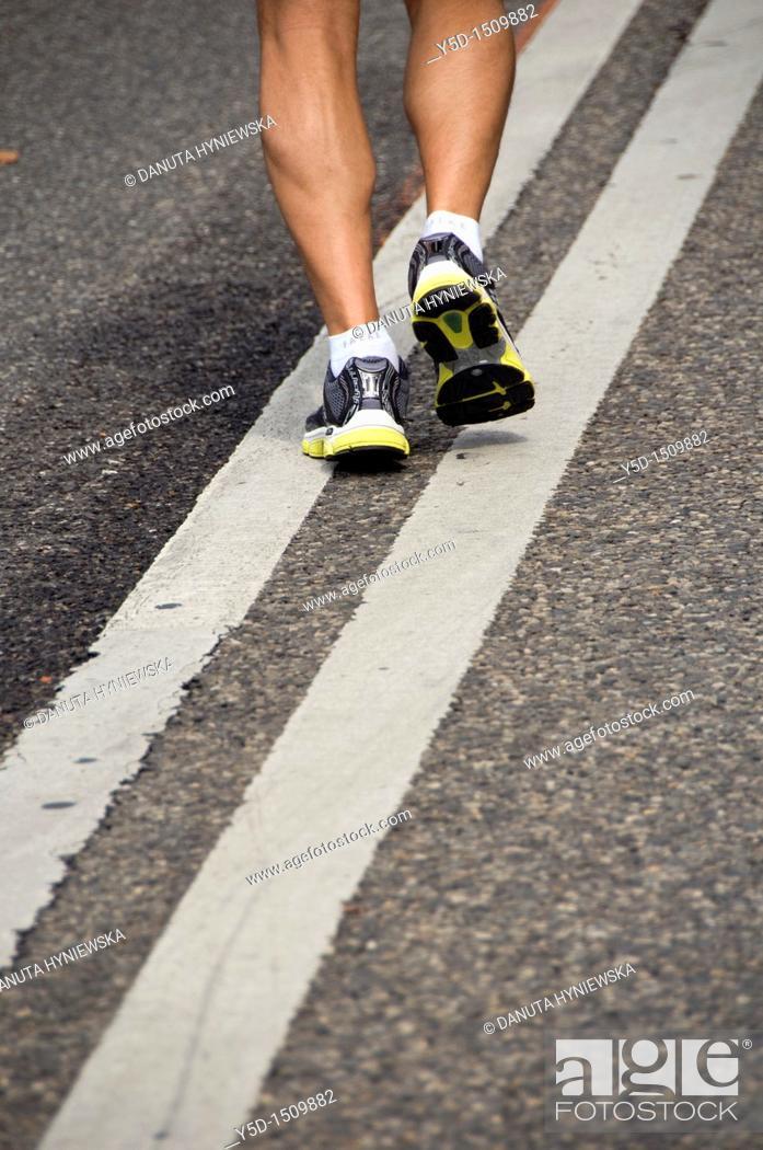Stock Photo: man running the street, legs only, Geneva, Switzerland.
