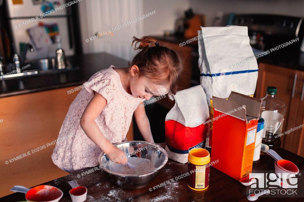 Stock Photo: Messy girl in kitchen stirring bowl of flour.