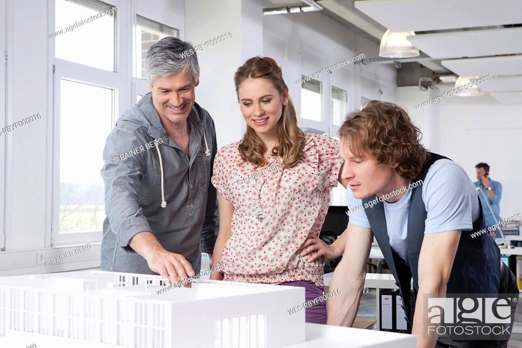 Stock Photo: Germany, Bavaria, Munich, Man explaining architectural model to colleagues.
