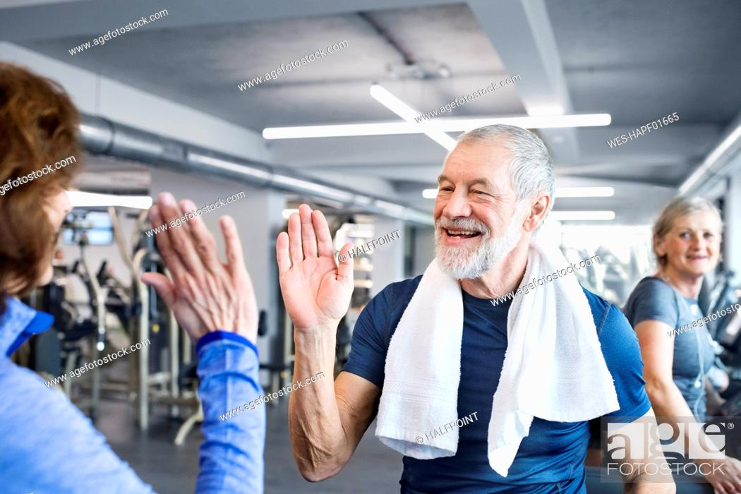 Imagen: Happy senior man and woman high fiving after working out in gym.
