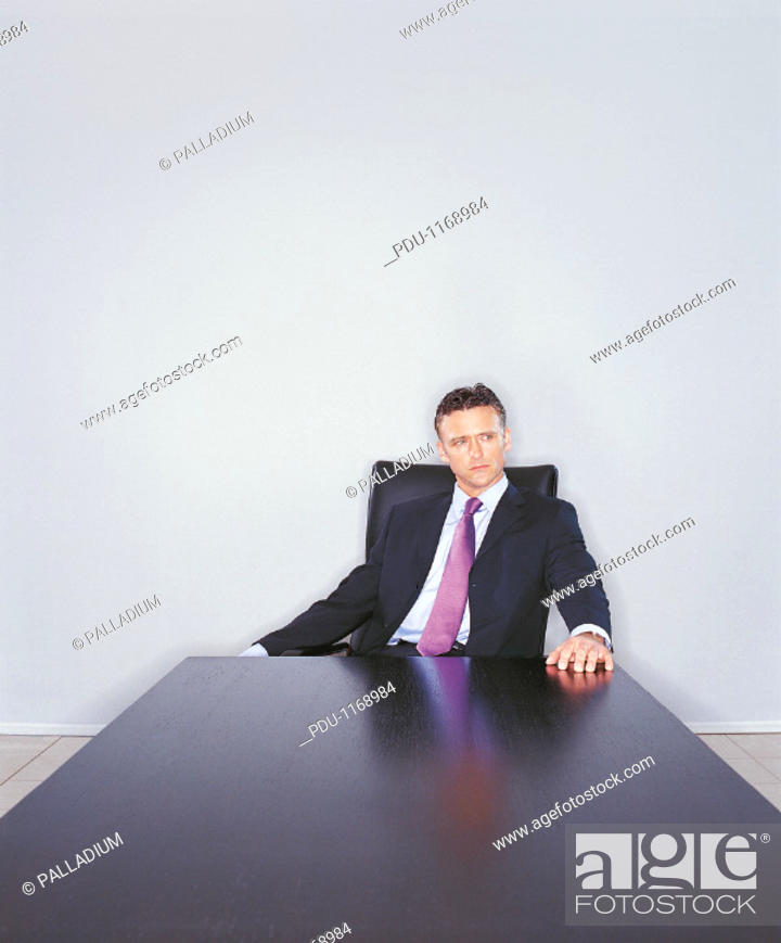 Stock Photo: Mature Ceo Sitting at the End of a Long Table and Looking Sideways.