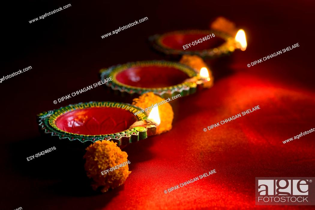 Stock Photo: Happy Diwali - Clay Diya lamps lit during Diwali celebration. Greetings Card Design of Indian Hindu Light Festival called Diwali.