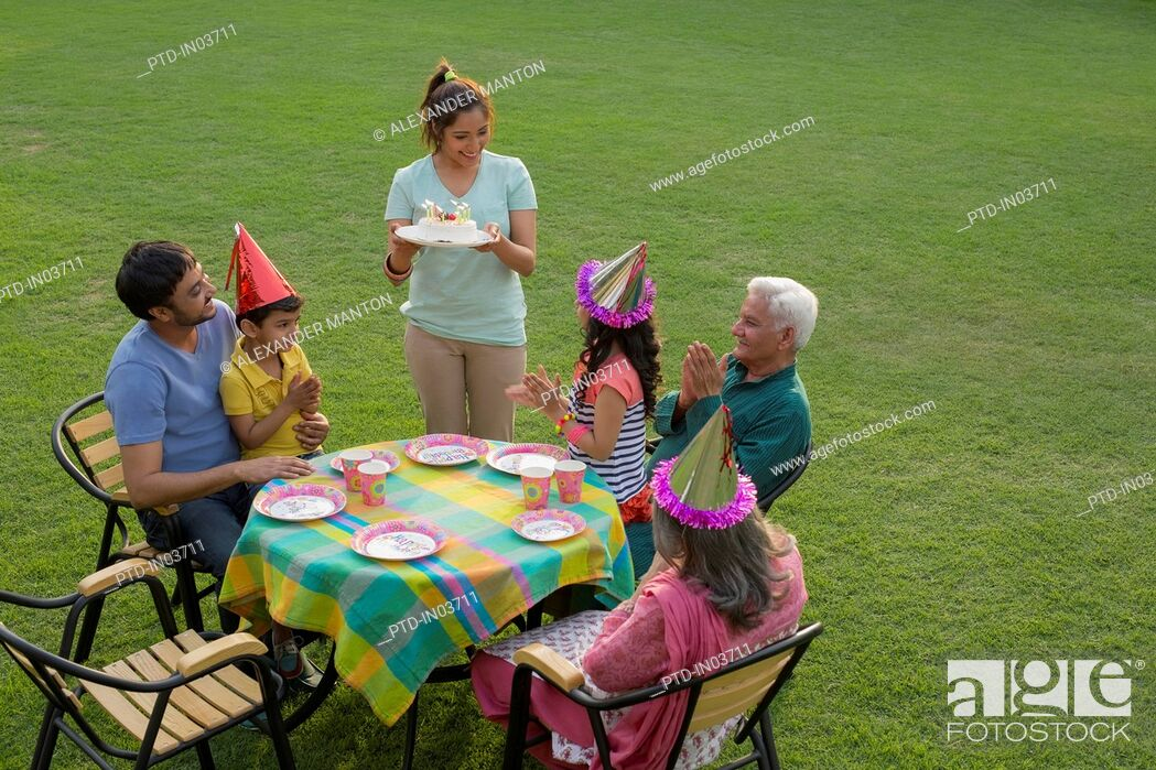 Stock Photo: Mother holding birthday cake at party table with children (4-5), outside.