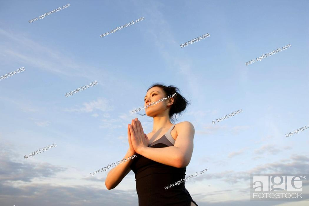 Stock Photo: Low angle view of young woman performing yoga.