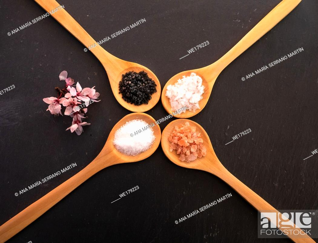 Imagen: Wooden spoons with himalayan salt, black hawaii salt, common salt and salt flakes on a slate plate.
