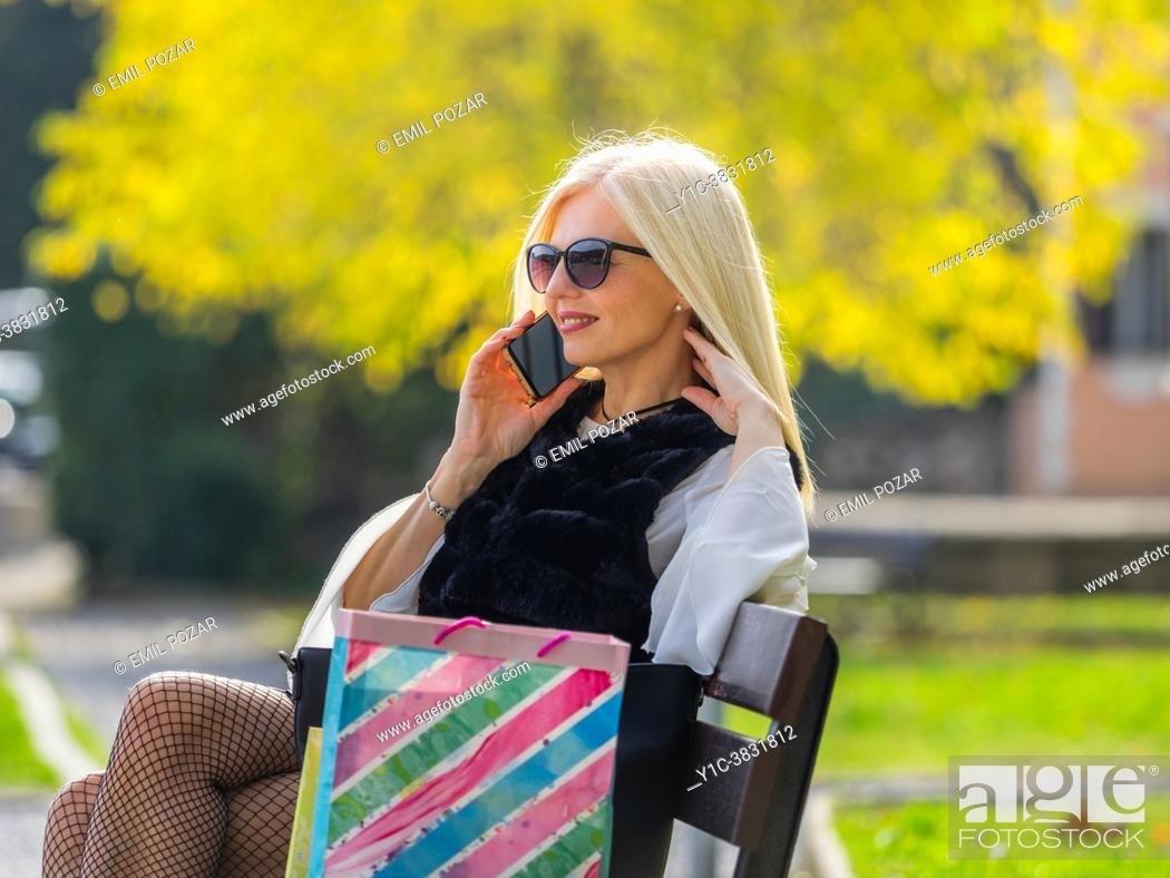 Stock Photo: Attractive blonde woman in park with shopping bags smartphone conversation.