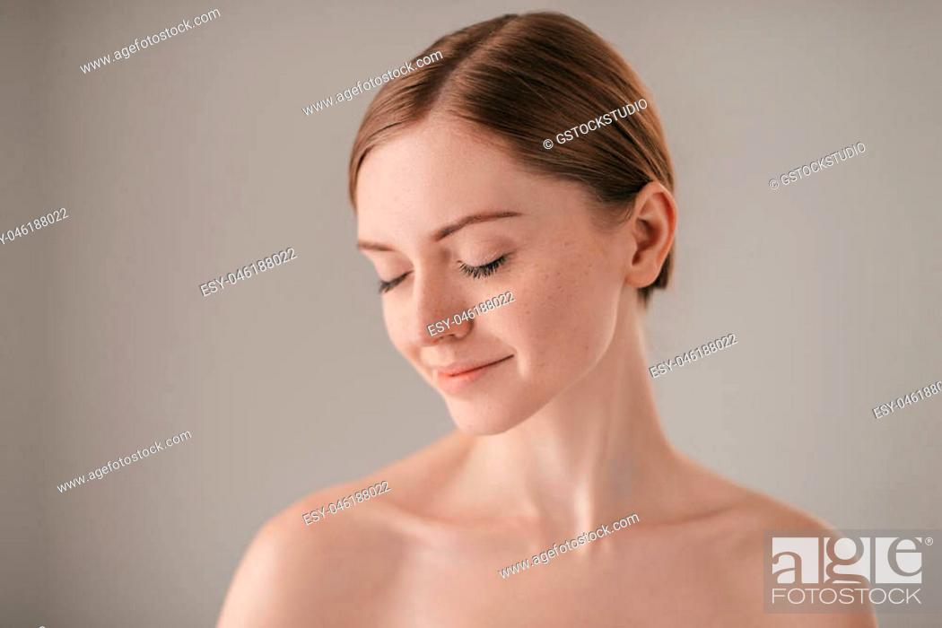 Stock Photo: Calm and beautiful. Portrait of redhead woman with freckles keeping eye closed and smiling while standing against grey background.