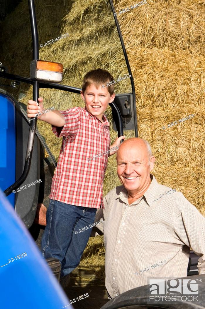 Stock Photo: Portrait of farmer and grandson near tractor and hay.