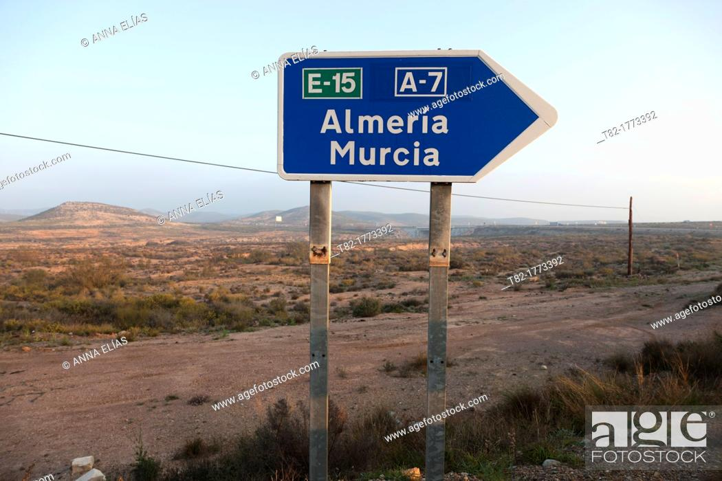 Stock Photo: Desert landscape with blue road sign pointing provinces of Andalusia, Almeria, Murcia, Andalucia, Spain, Europe.