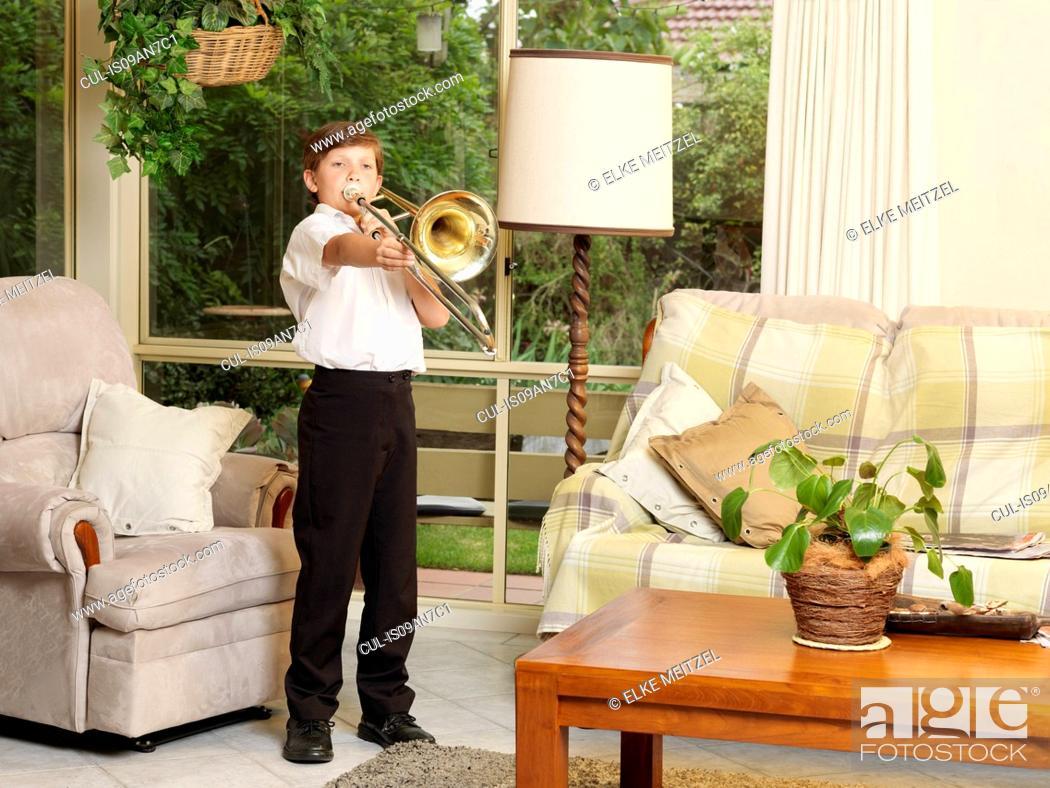 Imagen: Boy playing trombone in sitting room.