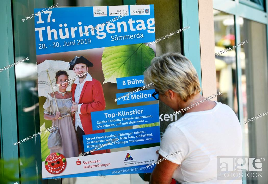Stock Photo: 28 June 2019, Thuringia, Sömmerda: A woman hangs a poster for Thuringia Day on a shop floor. The Thuringia Day takes place from 28.06.2019 to 30.06.