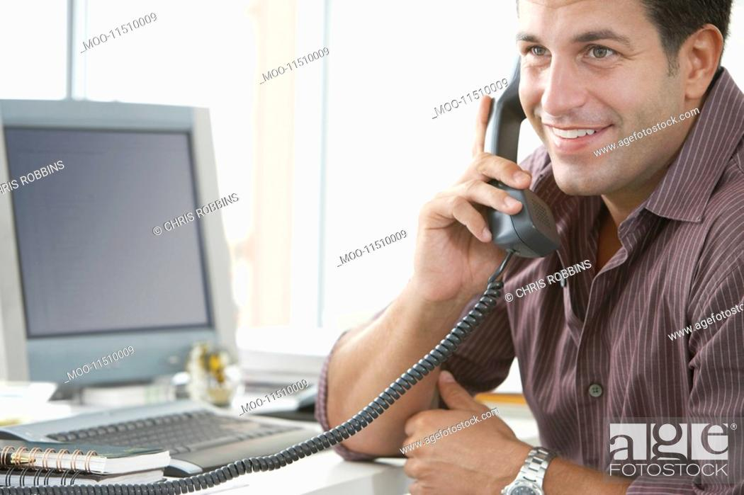 Stock Photo: Businessman using telephone at desk in office.