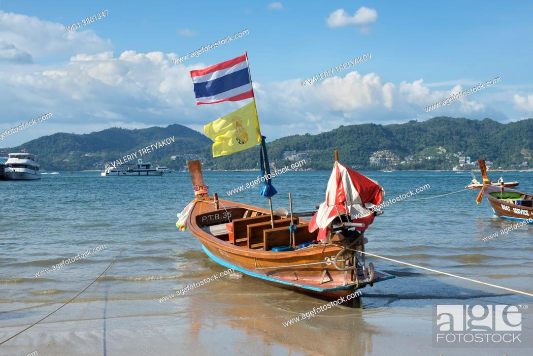 Stock Photo: Phuket, Thailand Traditional longtail boat with national flag on the shore of Patong beach at Andaman sea, Phuket island in Thailand.
