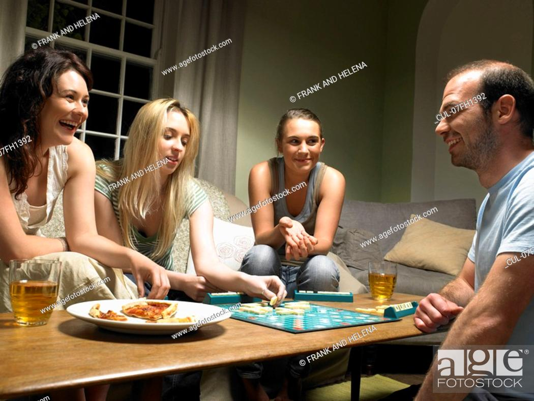 Stock Photo: Four young people playing scrabble.