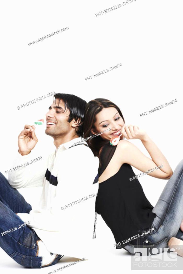 Stock Photo: Side profile of a young couple sitting back to back holding lollipops.
