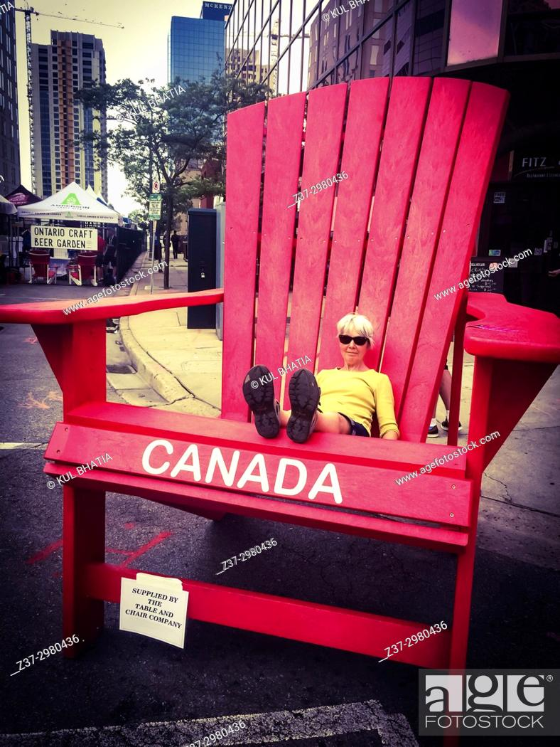 Stock Photo - A woman sits in an oversized giant adirondack chair set out for a street party Ontario Canada. & A woman sits in an oversized giant adirondack chair set out for a ...