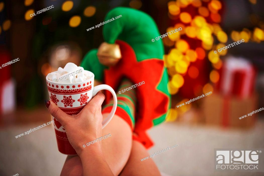 Stock Photo: Woman wearing elf slippers holding hot chocolate.