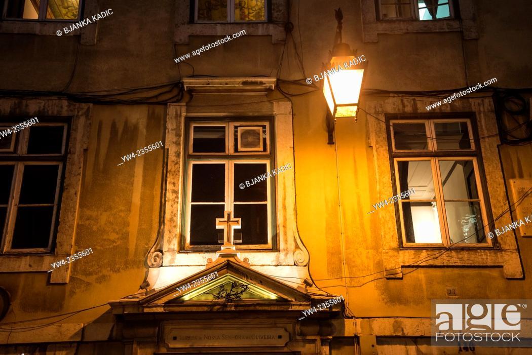 Stock Photo: Cross and lantern at night, Igreja de Nossa Senhora da Oliveira, Lisbon, Portugal.