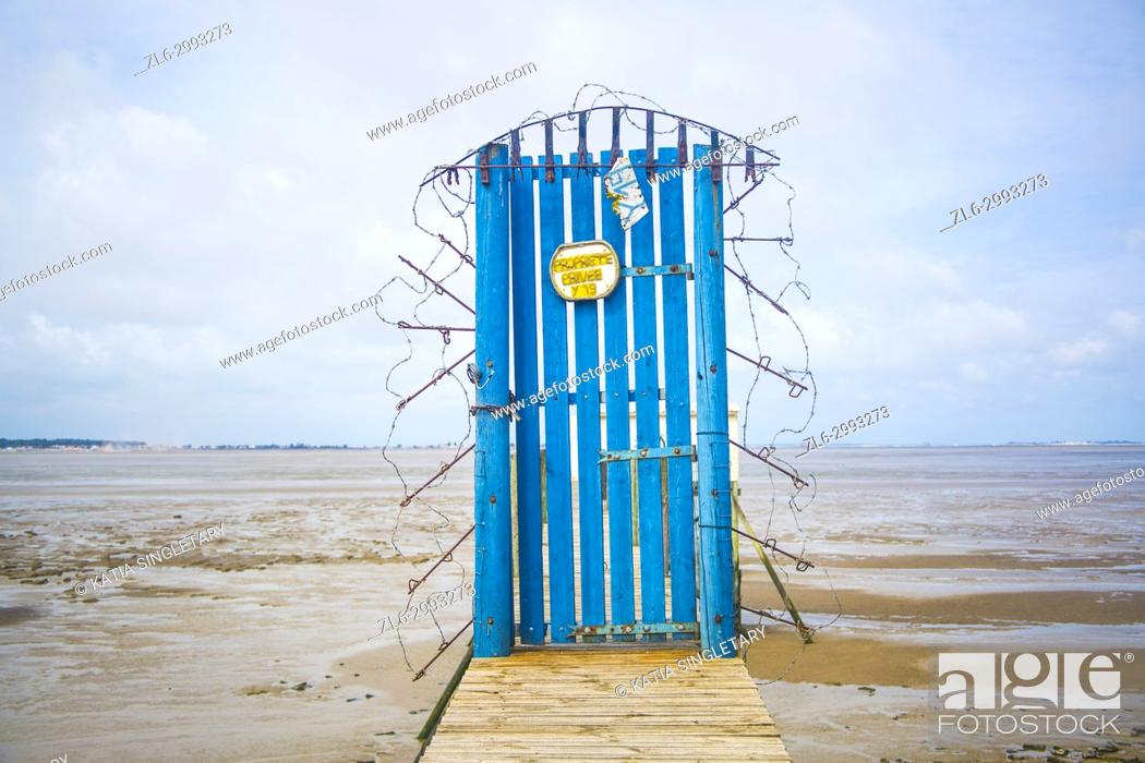 Stock Photo: Bright blue door in the middle of a pier with barb wire. Very compelling emotion and concept of Hell. Tide is down, water is brown.