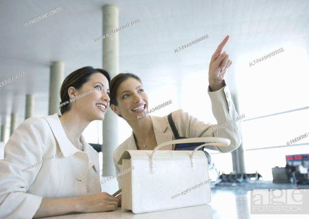 Stock Photo: Two women in airport, one pointing.