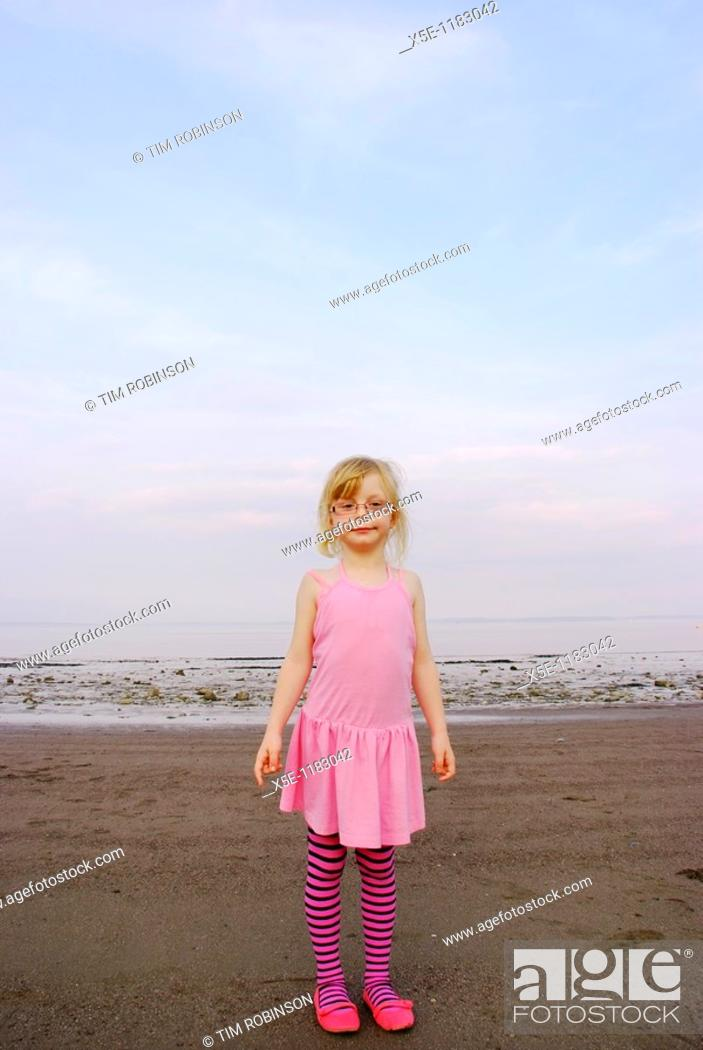 Stock Photo: Portrait of 7 year girl wearing pink dress and tights at beach looking at camera.