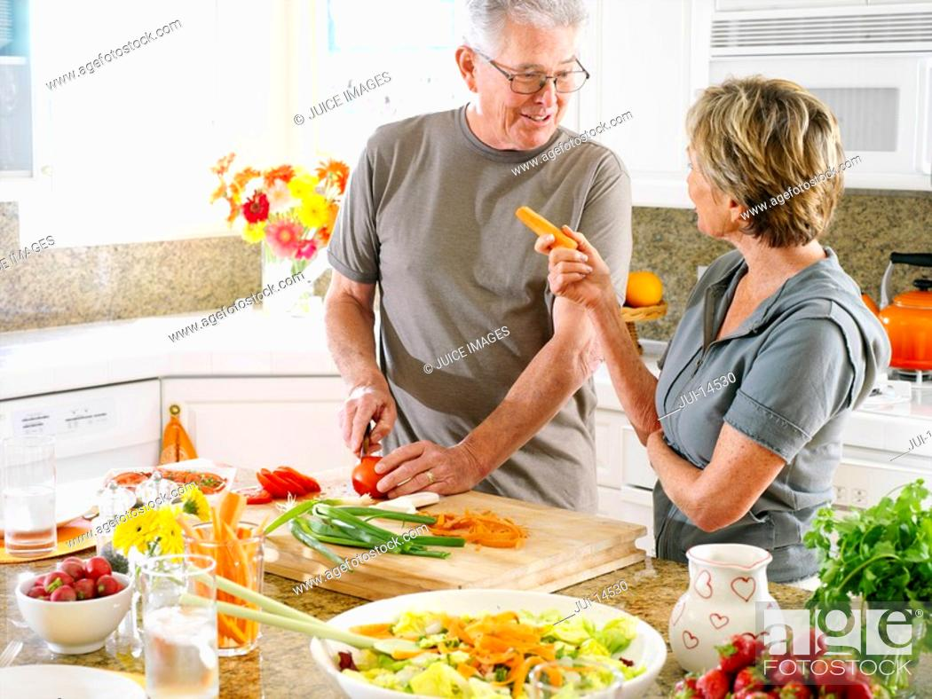 Stock Photo: Senior couple cooking in kitchen, smiling at each other.