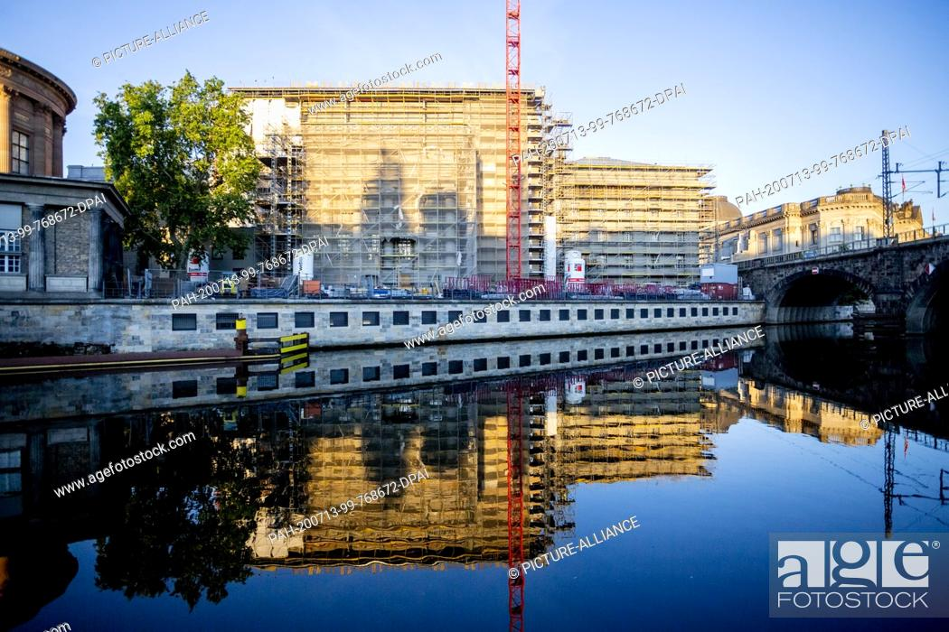 Imagen: 13 July 2020, Berlin: The Pergamonmuseum, which is currently under construction, is reflected in the light of the rising sun in the Spree.