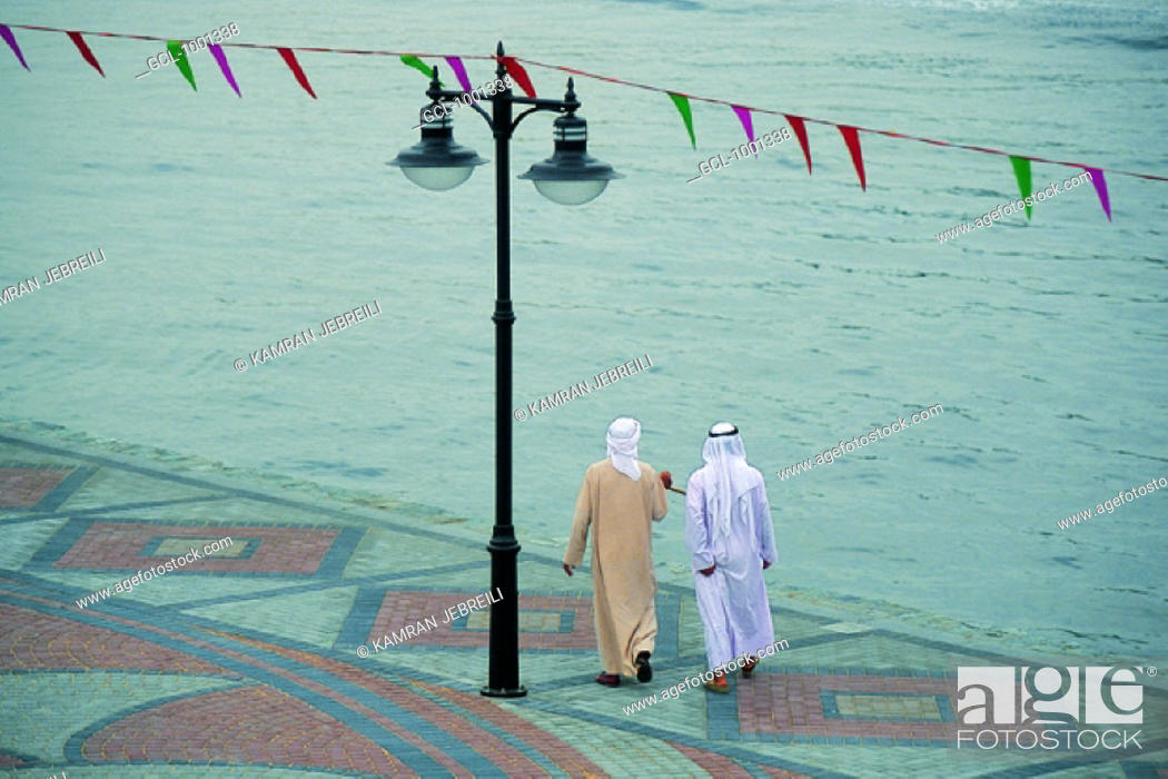 Stock Photo: Two Arab men going for a walk at the creek in Dubai, UAE.