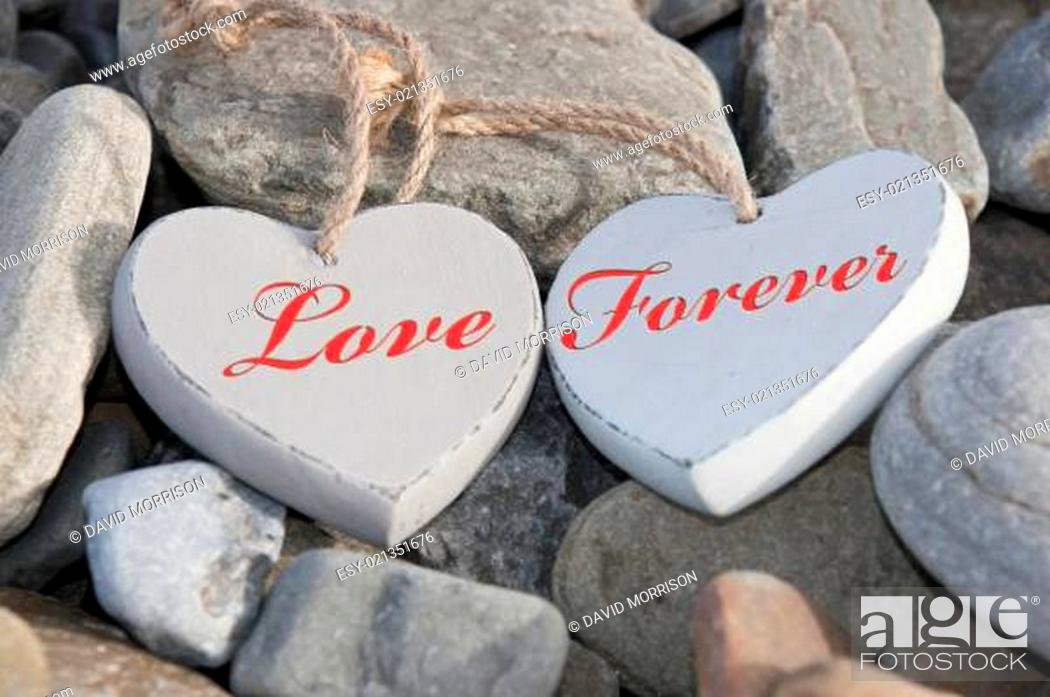 Stock Photo: two love hearts on a rocky beach as one.