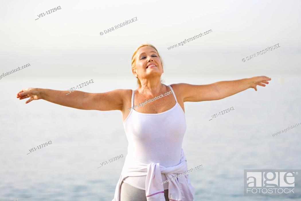 Stock Photo: Portrait of a senior adult woman stretching at the beach.