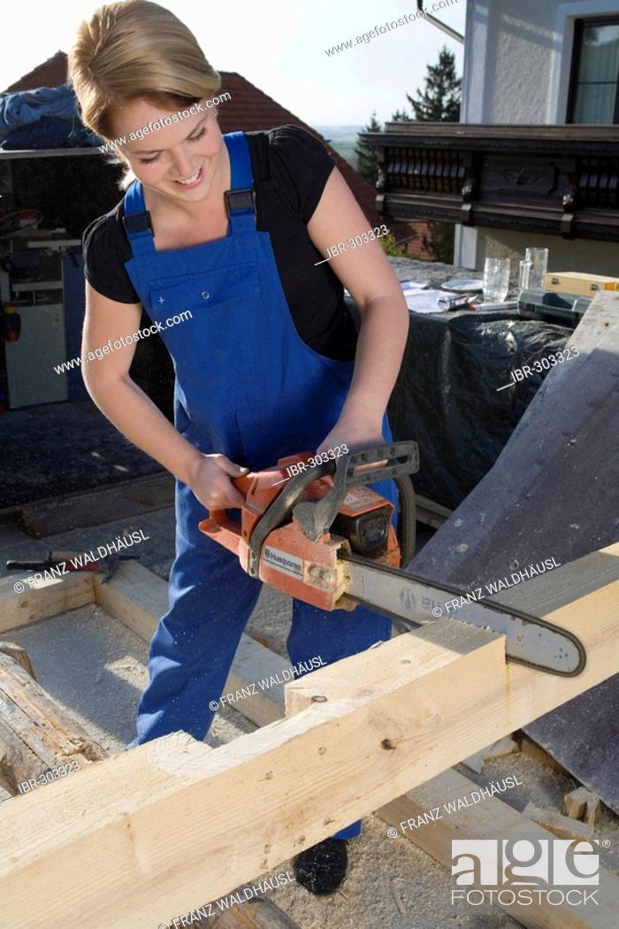 Stock Photo: Young woman works with a chain saw.