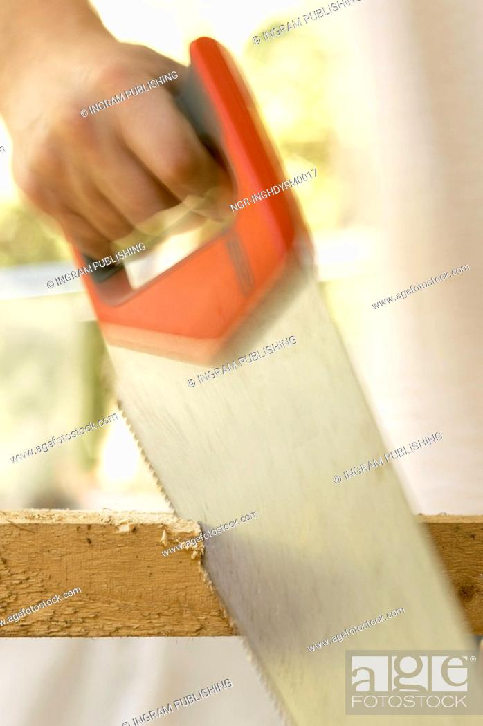 Stock Photo: Close-up of a man's hand using a hand saw on a piece of wood.