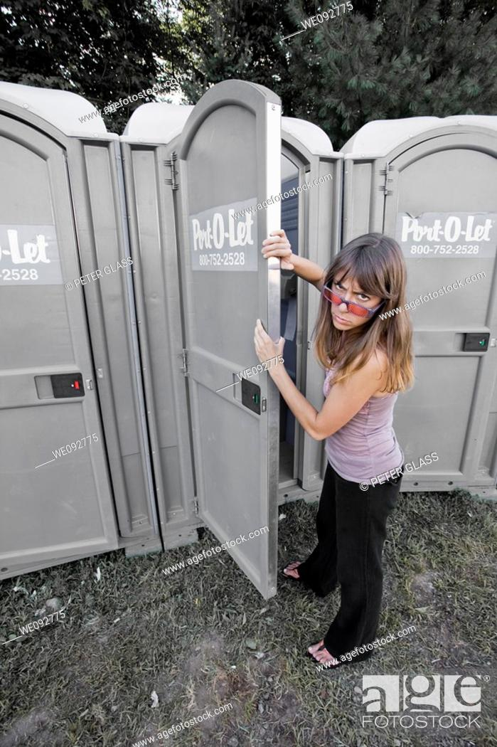Stock Photo: Young woman about to enter a portable toilet.