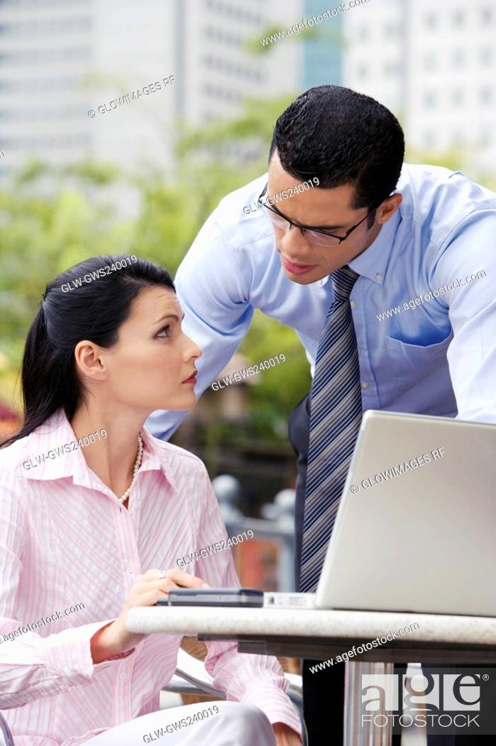 Stock Photo: Businesswoman using a laptop with a businessman standing beside her.