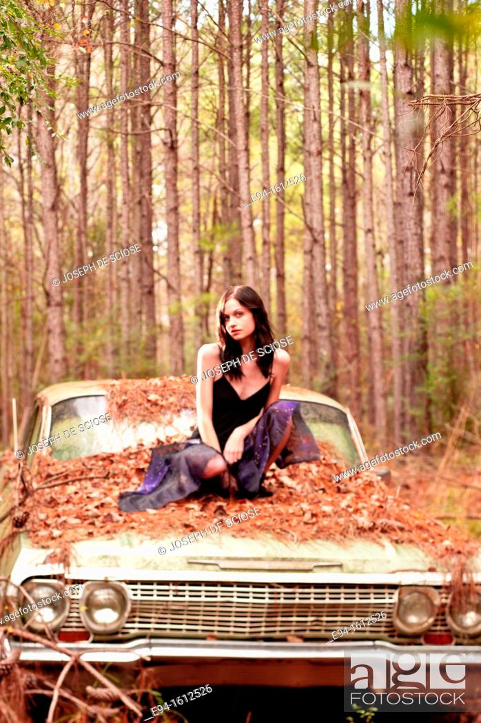 Stock Photo: Portrait of a 20 year old brunettte woman sitting on an old car in a forest setting.