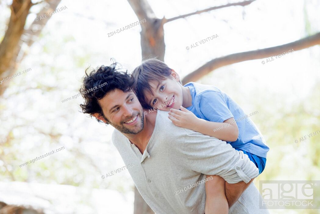 Stock Photo: Father giving little boy piggyback ride.