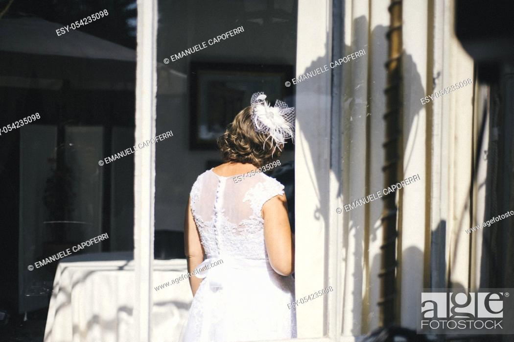 Stock Photo: Bride behind glass window an old villa, Lombardy, Italy.