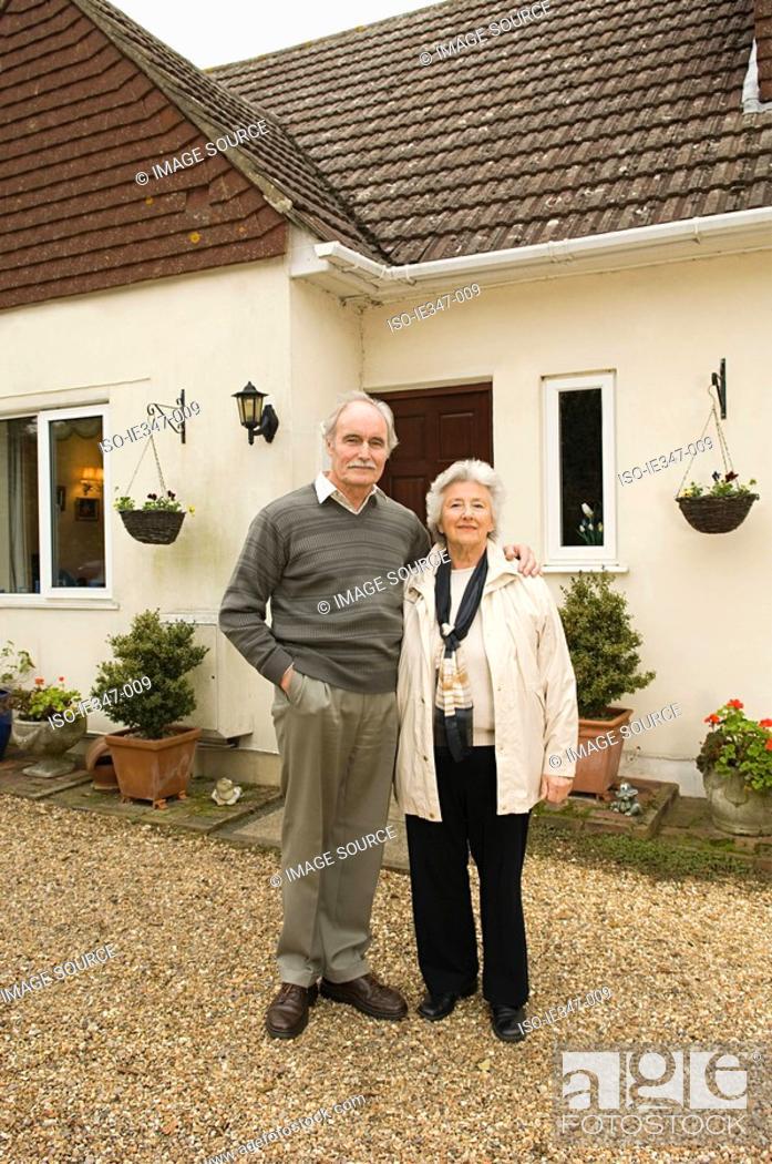 Stock Photo: Senior couple outside house.