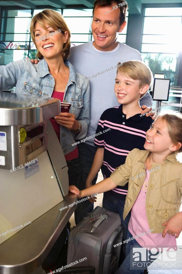 Stock Photo: Family checking in at airport check-in counter, smiling.