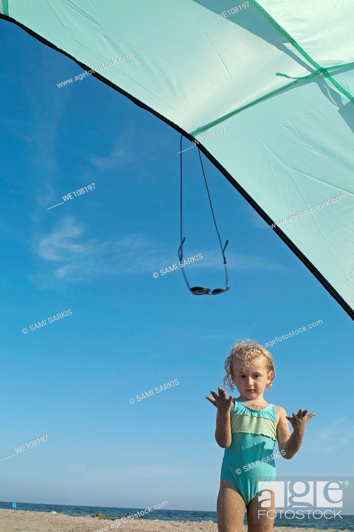 Stock Photo: Little girl playing under a sunshade at the beach, Camargue, France.