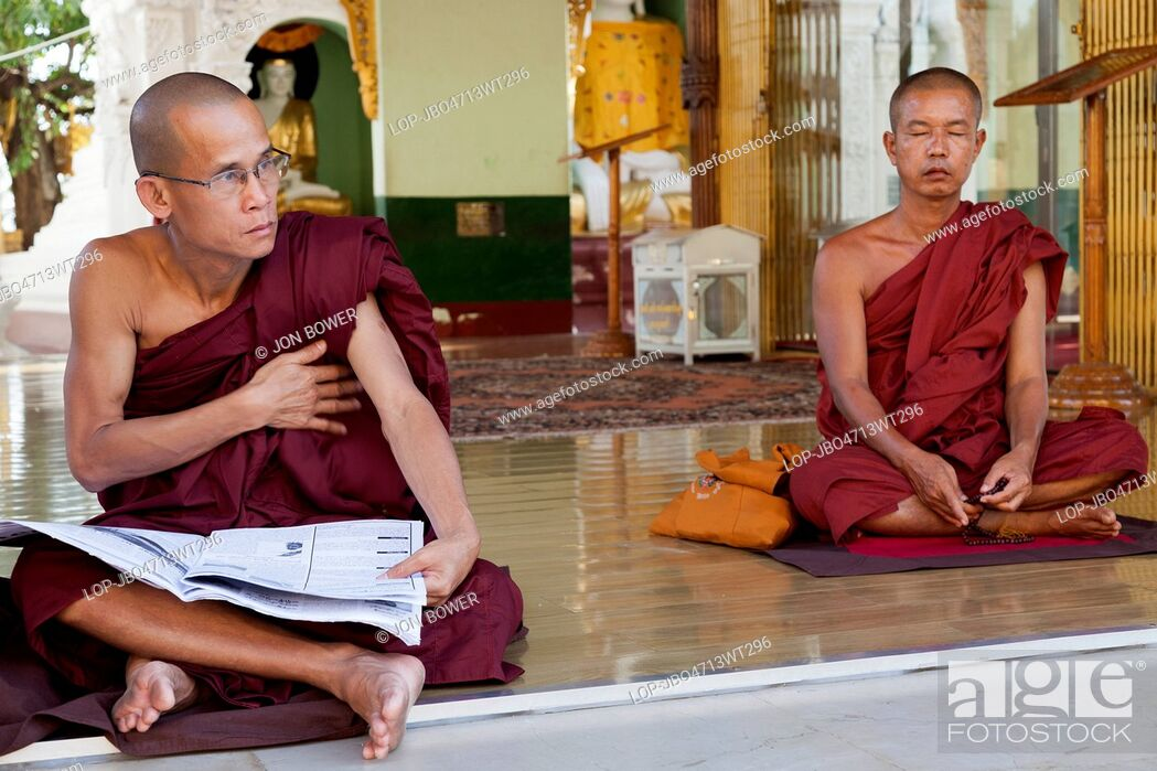 Imagen: Myanmar, Yangon, Yangon. Two monks with one meditating and one reading a newspaper at the Shwedagon Pagoda in Yangon in Myanmar.