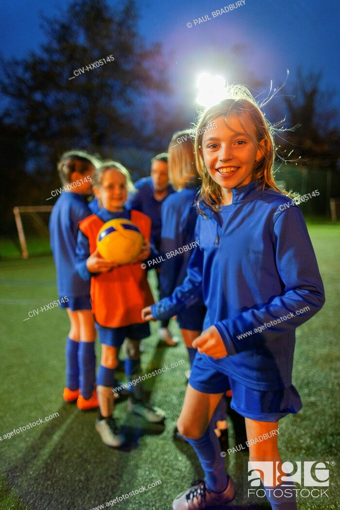 Photo de stock: Portrait smiling, confident girl soccer player practicing with team on field at night.